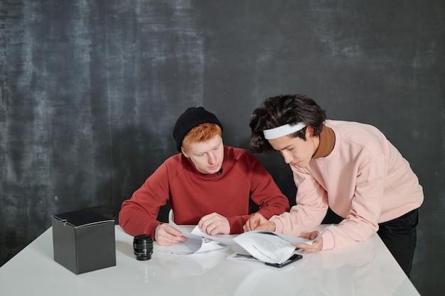 Deux jeunes hommes par 24 à la recherche de papiers avec discours tout en se préparant pour le tournage vidéo en studio