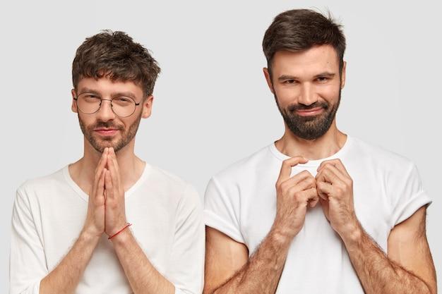 Deux jeunes hommes séduisants et mal rasés ont un regard intrigant, gardent les mains jointes, vêtus de vêtements décontractés, isolés sur un mur blanc. beaux hipsters posent à l'intérieur