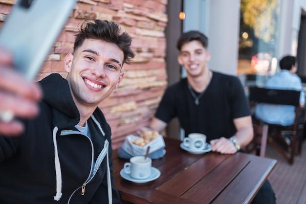 Deux jeunes hommes souriants en prenant un selfie dans un bar extérieur.