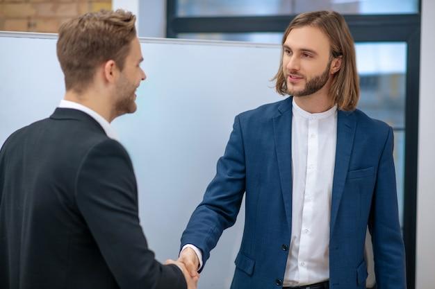 Deux jeunes hommes à succès adultes en costumes sombres et chemises blanches se serrant la main à l'intérieur au bureau