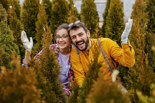 Deux jeunes jardiniers souriants accroupis entourés d'arbres à feuilles persistantes.
