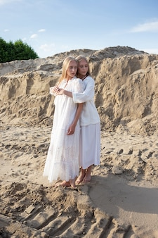 Deux jeunes jolies jumelles aux longs cheveux blonds posant à la carrière de sable dans d'élégantes robes blanches