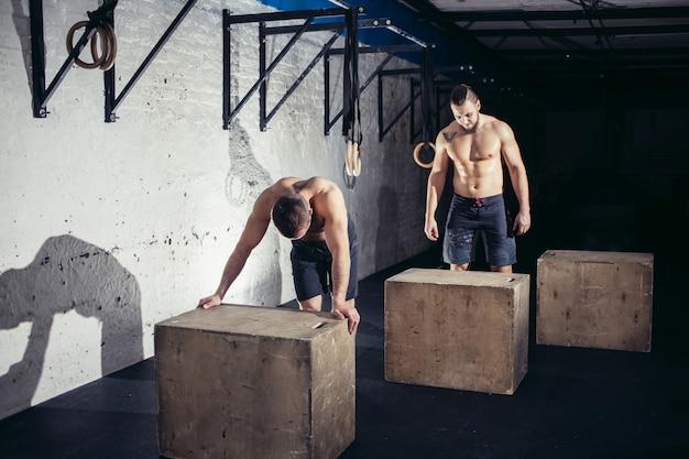 Deux jeunes jolis hommes fatigués après un saut de boîte au gymnase
