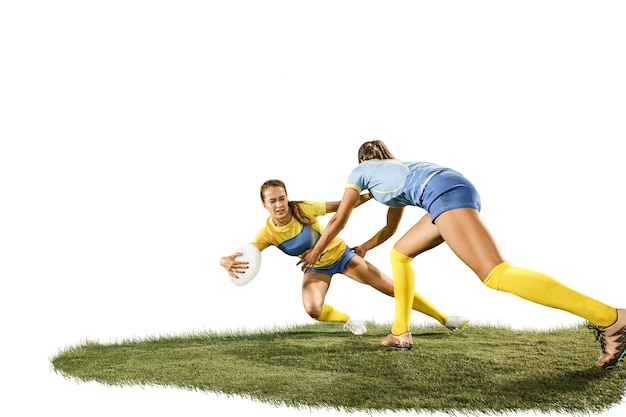 Les deux jeunes joueuses de rugby isolées sur fond de studio blanc avec de l'herbe verte. émotions humaines. filles en forme de race blanche. compétition sportive, mouvement, mouvement, combat, confrontation, attaque