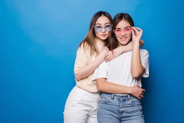 Deux jeunes meilleurs amis embrassant sur un mur bleu. jeunes femmes ayant du bon temps ensemble.