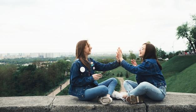 Deux jeunes meilleurs amis heureux s'amuser dans le parc de la ville