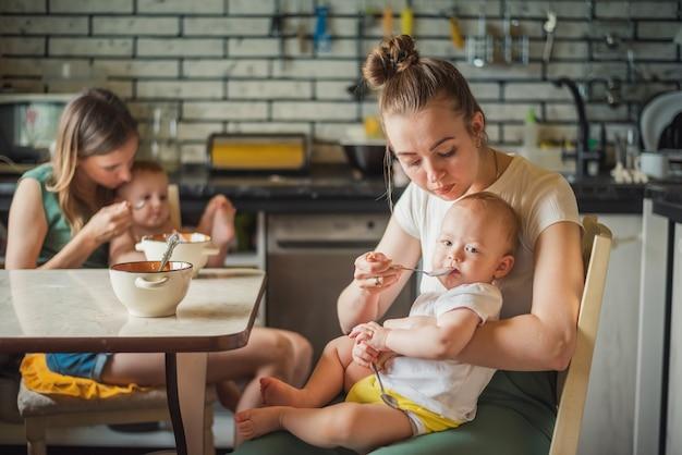 Deux jeunes mères ensemble nourrissent leurs bébés heureux bouillie de lait dans la cuisine