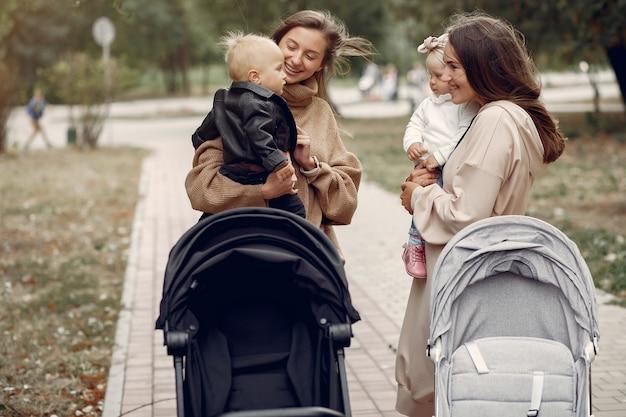 Deux jeunes mères marchant dans un parc en automne avec des calèches