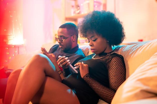 Deux jeunes milléniaux sérieux d'origine africaine utilisant des smartphones tout en envoyant des sms, en publiant ou en commentant sur les réseaux sociaux