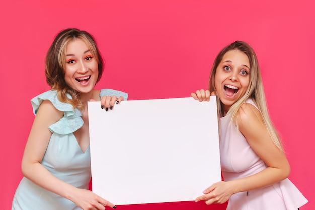 Deux jeunes promoteurs de femmes gaies assez souriantes tiennent un tableau blanc sur un mur rose de couleur vive