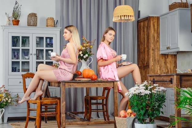 Deux jeunes sœurs assis dos à dos dans la cuisine