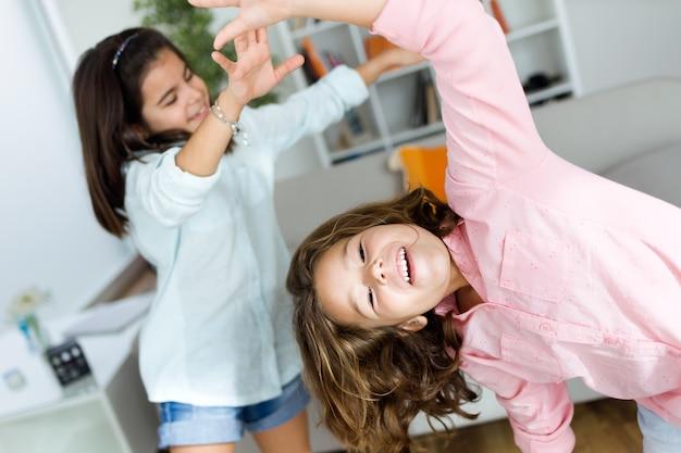 Deux jeunes soeurs écoutent de la musique et de la danse à la maison.