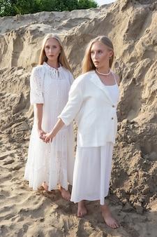 Deux jeunes soeurs jumelles attrayantes posant à la carrière de sable dans des vêtements blancs élégants