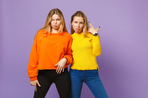 Deux jeunes sœurs jumelles blondes folles vêtues de vêtements colorés vifs soufflant des lèvres, montrant la langue isolée sur un mur bleu violet pastel. concept de mode de vie familial de personnes.