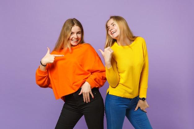 Deux jeunes sœurs jumelles blondes souriantes dans des vêtements colorés vifs se pointant du doigt isolés sur un mur bleu violet pastel. concept de mode de vie familial de personnes.