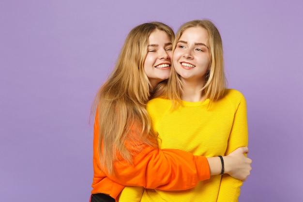 Deux jeunes sœurs jumelles blondes souriantes et joyeuses vêtues de vêtements colorés vifs étreignant en regardant de côté isolées sur un mur bleu violet pastel. concept de mode de vie familial de personnes.