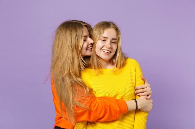 Deux jeunes sœurs jumelles blondes souriantes et souriantes dans des vêtements colorés vifs s'embrassant, regardant de côté isolées sur un mur bleu violet pastel. concept de mode de vie familial de personnes.