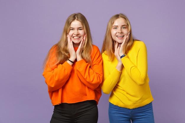 Deux jeunes sœurs jumelles blondes souriantes vêtues de vêtements colorés et vifs, mettant les mains sur les joues isolées sur un mur bleu violet pastel. concept de mode de vie familial de personnes.