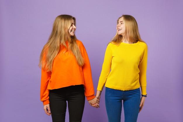 Deux jeunes sœurs jumelles blondes en train de rire dans des vêtements éclatants se regardant isolées sur un mur bleu violet pastel. concept de mode de vie familial de personnes.