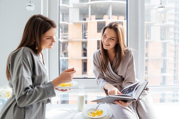 Deux jeunes sœurs jumelles souriantes regardant la photo dans le livre et prenant le petit déjeuner ensemble