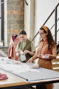 Deux jeunes tailleurs féminins en vêtements décontractés d'emballage de nouvelles épaulettes pour manteaux, vestes et robes en se tenant debout par table en studio