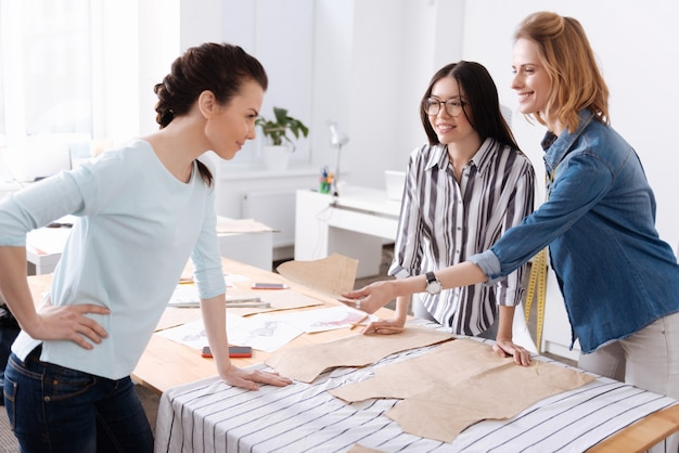 Deux jeunes tailleurs joyeux tendant en plaisantant un modèle de robe à leur collègue ayant une expression de colère moqueuse ludique