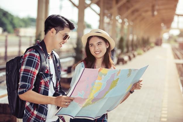 Deux jeunes touristes asiatiques avec des sacs à dos avec carte