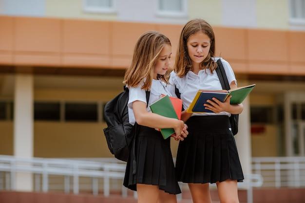 Deux jolies adolescentes en uniforme scolaire noir et blanc lisant des livres près de leur école.
