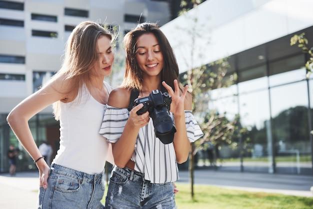 Deux jolies amies de la fille avec l'appareil photo prennent des photos ensemble et se promènent dans la ville.