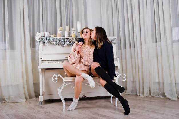 Deux jolies amies habillées en pull chaud et jambières