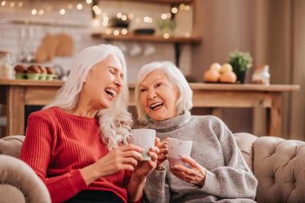 Deux jolies dames agréables aux cheveux gris assis sur le canapé et à la recherche incroyable