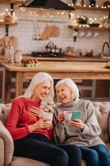 Deux jolies dames agréables aux cheveux gris assis sur le canapé et souriant