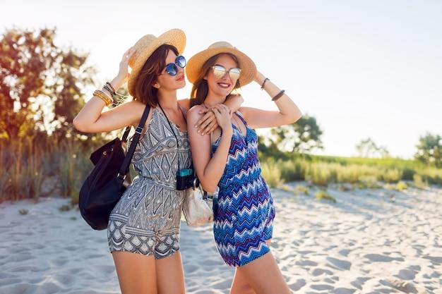 Deux jolies femmes avec appareil photo à la plage ensoleillée, profitant de vacances