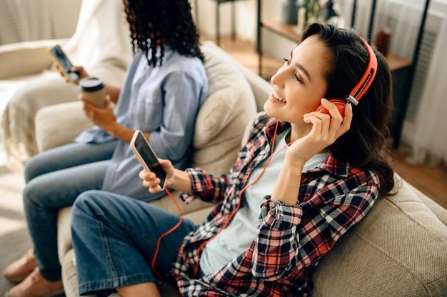 Deux jolies femmes dans les loisirs d'écouteurs sur le canapé