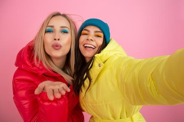 Deux jolies femmes posant sur fond rose en veste d'hiver colorée de couleur rouge et jaune vif, amis s'amusant ensemble, tendance de la mode des vêtements chauds, prenant selfie