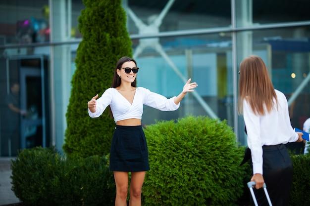 Deux jolies femmes se rencontrent près de l'aéroport