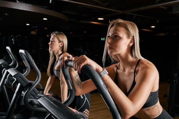 Deux jolies femmes sportives équitation vélos d'exercice pendant l'entraînement à vélo dans la salle de gym