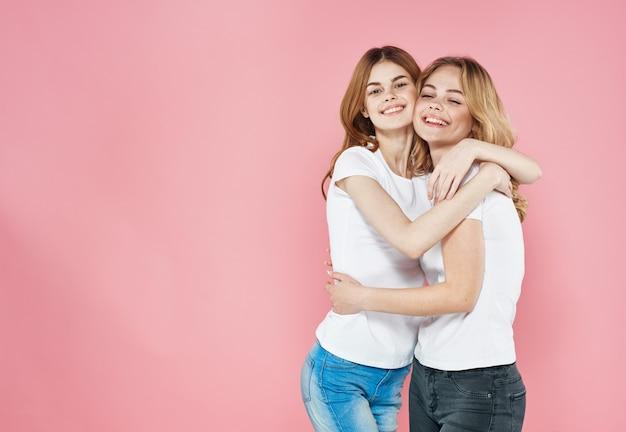 Deux jolies femmes vêtements de mode glamour amitié amusement rose