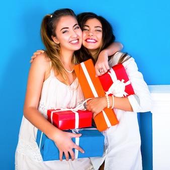 Deux jolies filles amis tenant des cadeaux de vacances lumineux