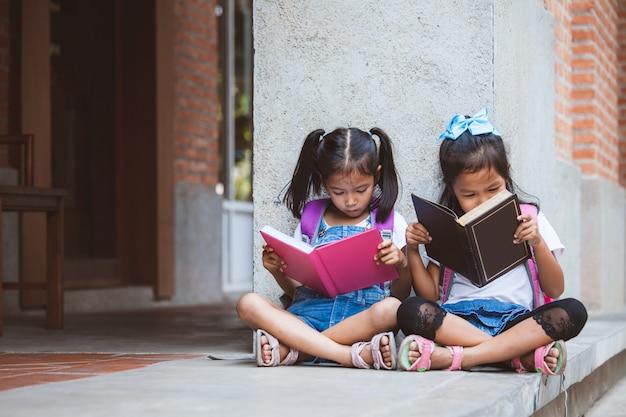 Deux jolies filles asiatiques lisant un livre ensemble à l'école avec plaisir et bonheur