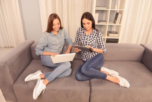 Deux jolies filles assises sur le canapé et travaillant sur un ordinateur portable