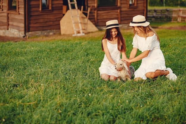 Deux jolies filles dans un champ avec une chèvre
