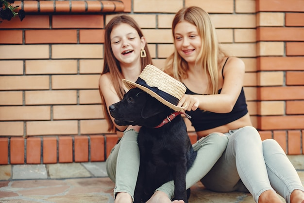 Deux jolies filles dans un parc d'été avec un chien