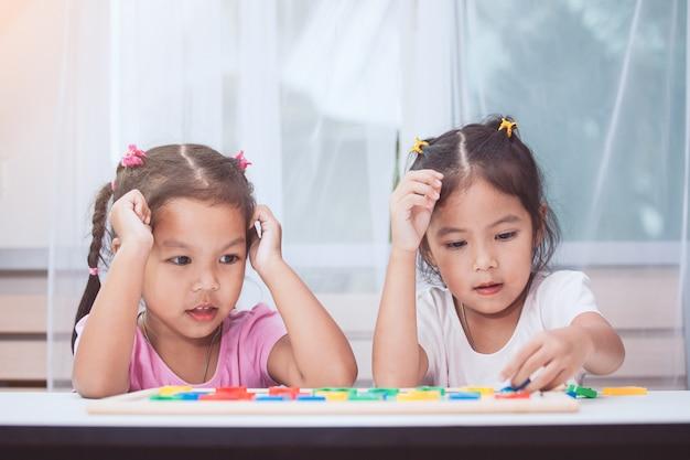 Deux jolies filles d'enfants asiatiques s'amuser à jouer et apprendre les alphabets magnétiques ensemble