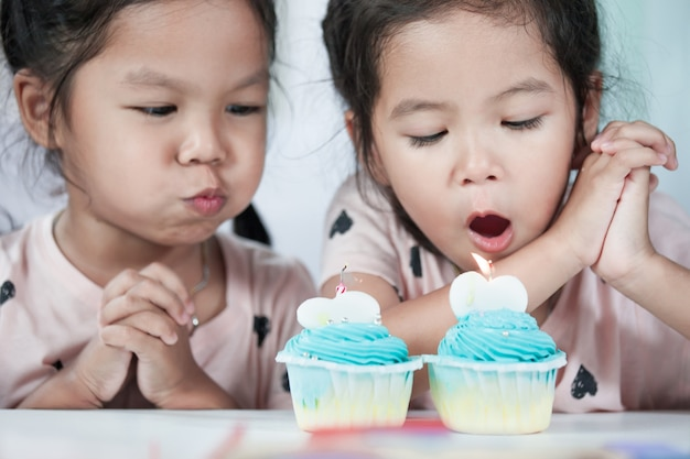 Deux jolies filles d'enfants asiatiques s'amuser à souffler le gâteau d'anniversaire ensemble dans le ton de couleur vintage