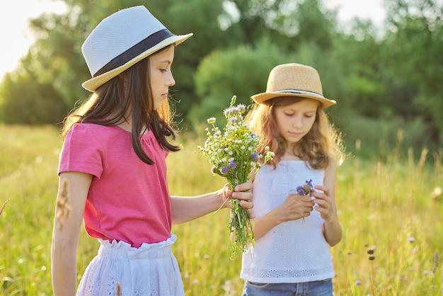 Deux jolies filles enfants marchant dans une prairie ensoleillée cueillant des fleurs sauvages dans un bouquet. vacances d'été, nature, enfance heureuse, concept d'amitié
