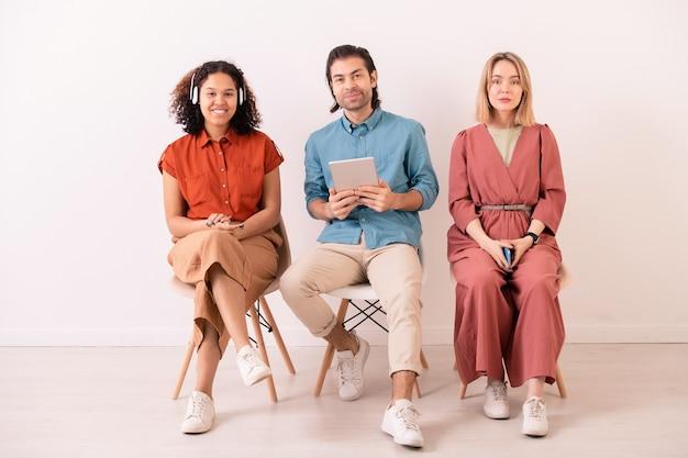 Deux jolies filles interculturelles et jeune homme avec tablette assis sur des chaises contre un mur blanc devant la caméra tout en s'amusant à loisir