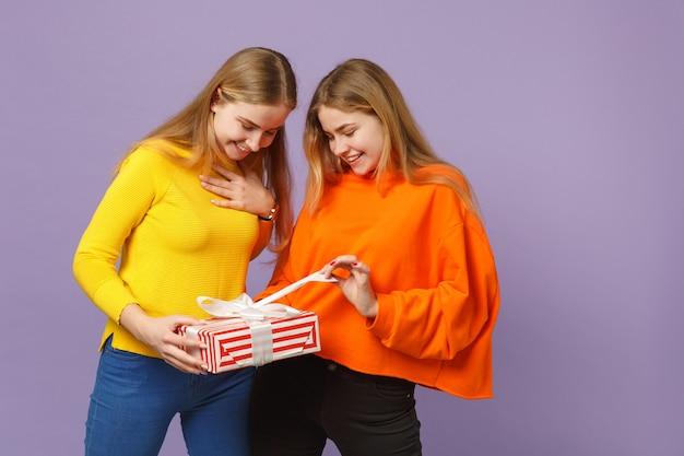 Deux Jolies Filles Jumelles Blondes Dans Des Vêtements Vifs Tenant Une Boîte Cadeau à Rayures Rouges Avec Un Ruban Cadeau Isolé Sur Un Mur Bleu Violet. Anniversaire De La Famille Des Gens, Concept De Vacances. Photo Premium