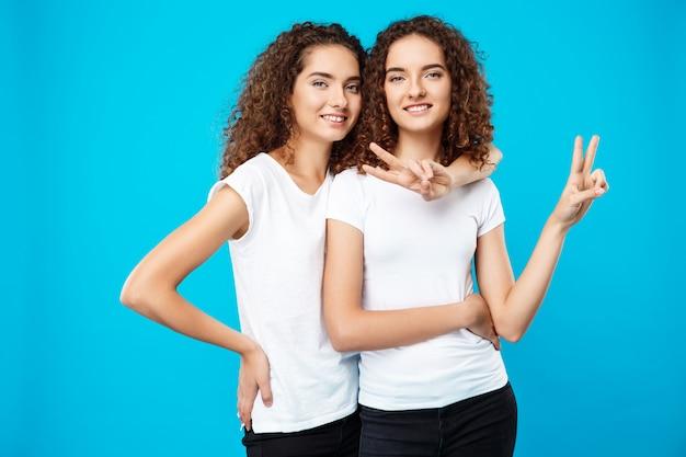 Deux jolies filles jumelles souriant, montrant la paix sur le mur bleu