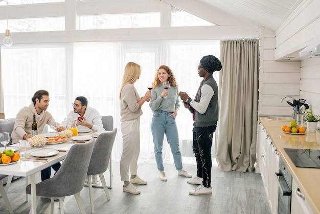 Deux jolies filles et mec africain avec du vin rouge debout dans la cuisine et ayant parler pendant que leurs amis assis par table servie